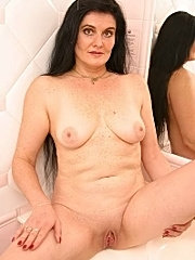 Mature brunette masturbating in bath-room.