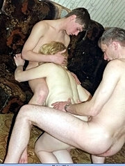Blonde mom undressing and having sex with two boys, taking their cocks from both sides at the same time