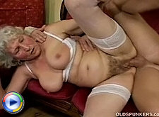 Mature blonde lady on gold old sofa licking boobs