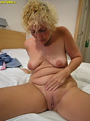 Blue eyed mature vixen stuffs dildos into both her mature holes